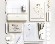 white stationery products laid out. no other color than hues of white & shadow is present
